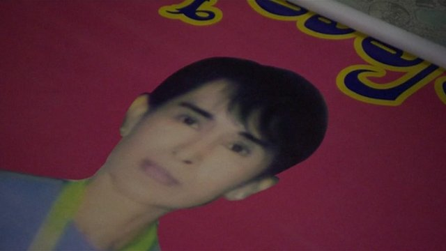 Poster of Aung San Suu Kyi rolled out on the floor