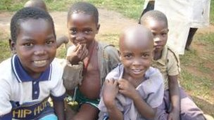 Children sitting on ground and smiling