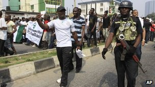 A police officer walk with protesters on fourth day of a nationwide strike in Lagos, Nigeria, 12 January 2012