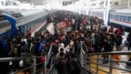 People prepare to board a train at the Beijing West Railway Station in China, 7 January 2012