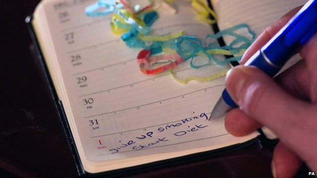 Person writing new year resolutions for 2012 in a diary