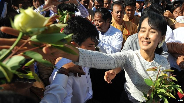 Aung San Suu Kyi takes flowers from supporters