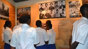 Rwandan school children looking at a display about genocides around the world