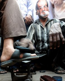 A cobbler wearing a Salman Rushdie mask polishes shoes outside a mosque during a protest by an Islamic organisation in Mumbai on January 11, 2011.