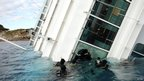 Scuba divers inspect the interior of the Costa Concordia cruise ship through a breach in a window (18 Jan 2012)
