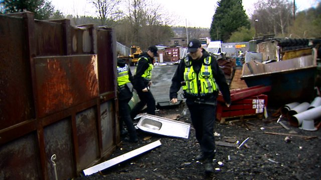 Police inspect a scrap metal dealer's yard