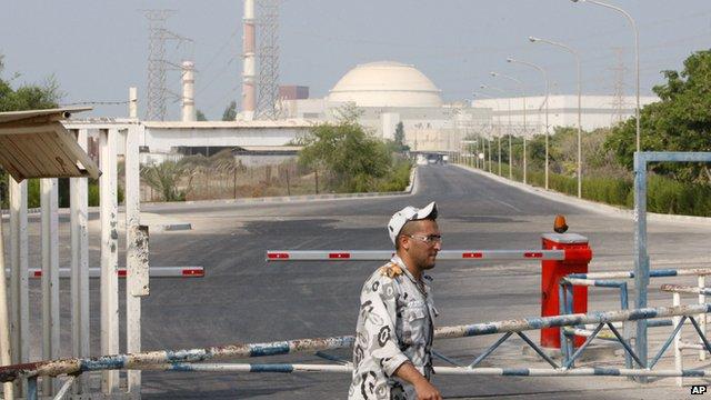 An Iranian security guard walks past Iran's Bushehr nuclear power plant