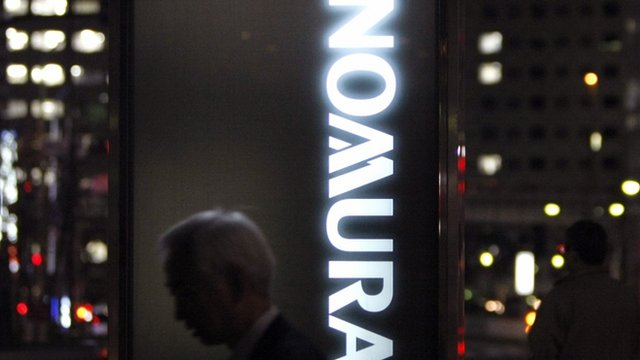 A man walks past a Nomura Securities sign in Tokyo