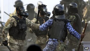 A Maldives police officer, in blue, charges soldiers during a clash in Male, Maldives, Tuesday, Feb. 7, 2012