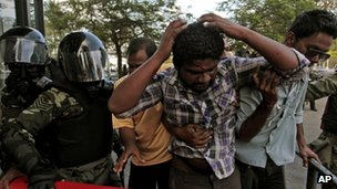 Supporters of former Maldivian President Mohamed Nasheed help a wounded protester as soldiers man a barricade near Republic Square in Male, Maldives, Wednesday, Feb. 8, 2012.