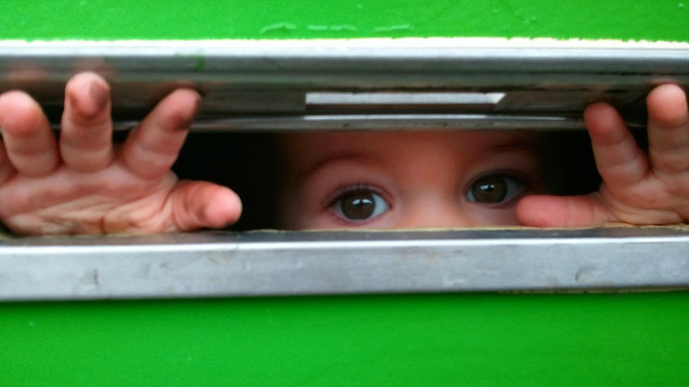 A child peering through a letter box with grubby fingers