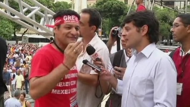 A TV presenter interviewing one of the striking workers