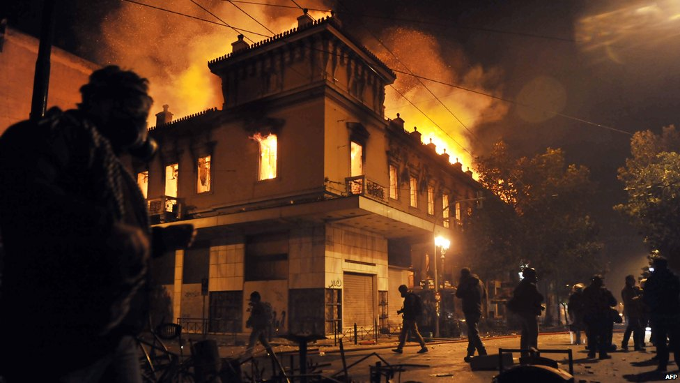 A fire engulfs a store during clashes between protesters and riot police near the Greek parliament in Athens on February 12, 2012