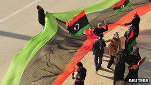 Libyans wave Kingdom of Libya flags as they celebrate the first anniversary of the uprising that toppled Muammar Gaddafi