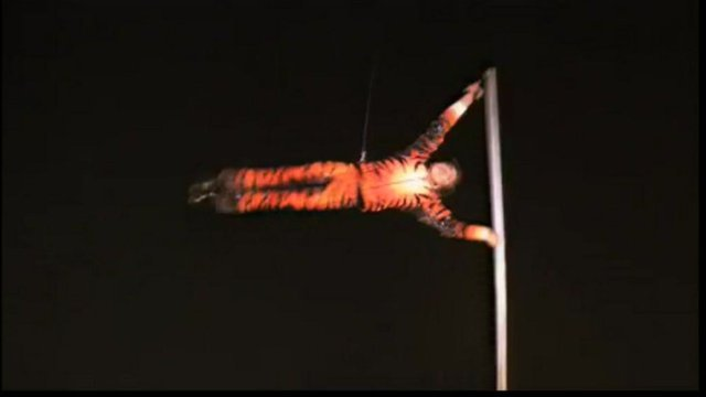 Man in tiger suit spins horizontally around a vertical pole.