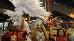 A member of the Renascer samba school is helped with her costume before the parade