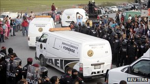 Mexican riot police stand guard as Forensic Medical Service vans drive out of the Apodaca prison