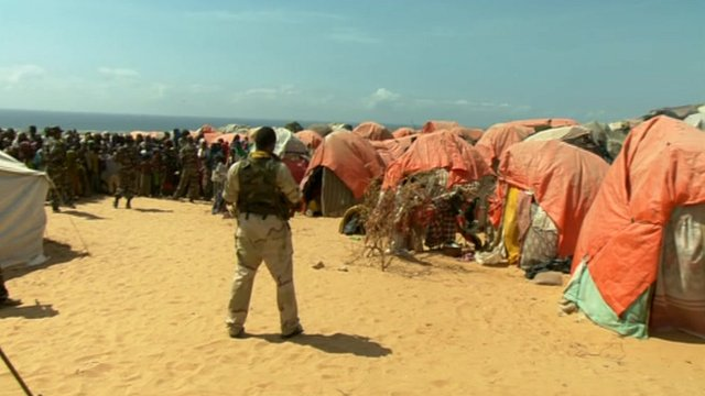 An armed soldier guards a Somali refugee camp