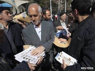 Iranians are handed election leaflets after Friday prayers in Tehran
