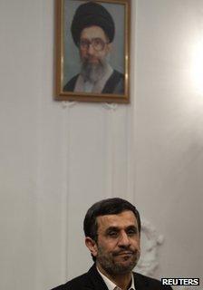Mahmoud Ahmadinejad sits in front of a portrait of Ayatollah ali Khamenei