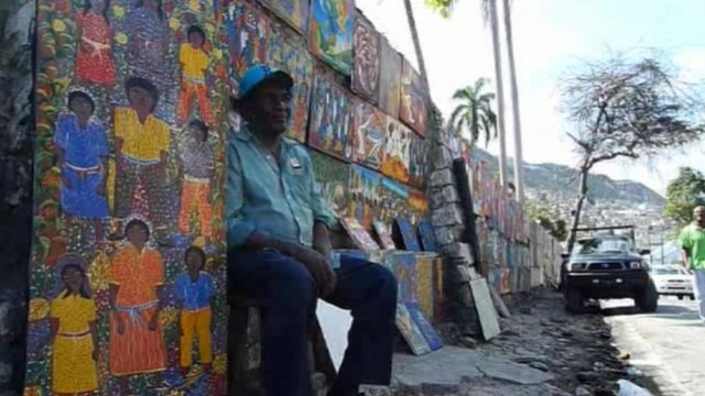 An artist selling his paintings in a street in Haiti