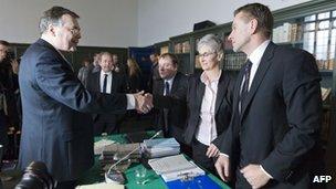 Iceland's ex-PM Geir Haarde shakes hands with Sigridur Fridjonsdottir, parliament prosecutor with her assistant Helgi Magnae's Gunnarsson in Reykjavik
