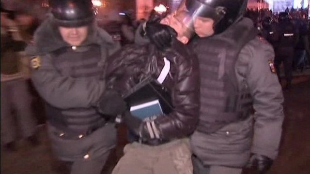 A demonstrator is arrested by two police in Moscow