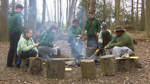 Children sitting around a campfire toasting sausages