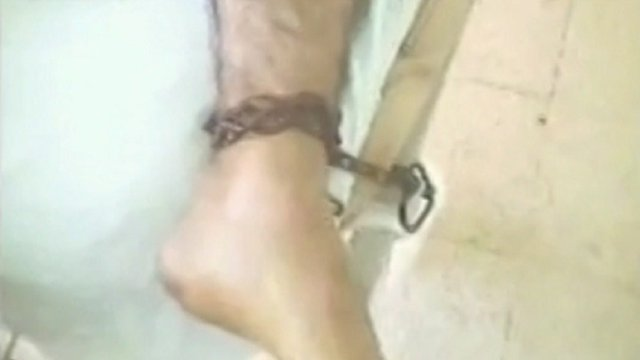 Picture from activist video purporting to show a wounded man chained to a hospital bed