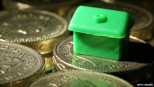 monopoly house resting on pound coins
