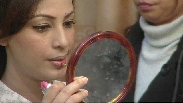 Farah Hussain, a Muslim Pakistani presenter, putting on make-up for her breakfast show.