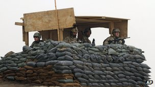 US and Afghan soldiers man a watch-tower at their base in Panjwai, Kandahar, 11 March