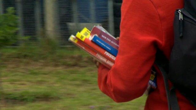 Girl in school uniform carrying books