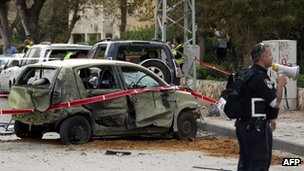 Israeli policeman stands near a car in Ashdod damaged by a rocket fired by militants in Gaza (12 March 2012)