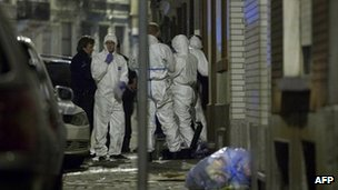 Police and members of a forensics team stand at the entrance to a mosque following petrol bomb attack in Anderlecht