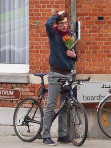 Man holding flowers in Heverlee, Belgium, 14 Mar 2012