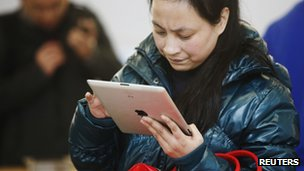 A customer tests out an Apple iPad at an Apple Store in downtown Shanghai, China 1 March 2012