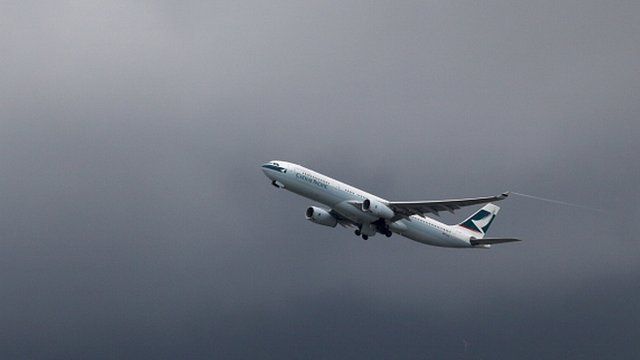 A Cathay Pacific aircraft takes off in grey skies from Hong Kong's international airport