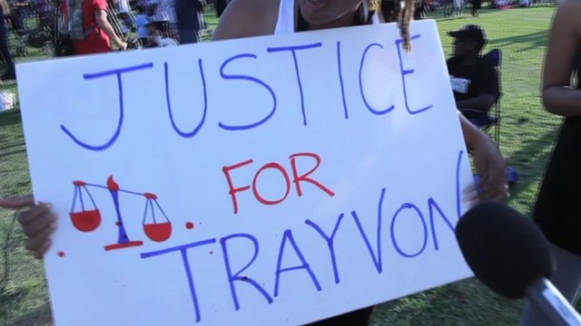 "Woman holds sign that reads ""Justice for Trayvon""."