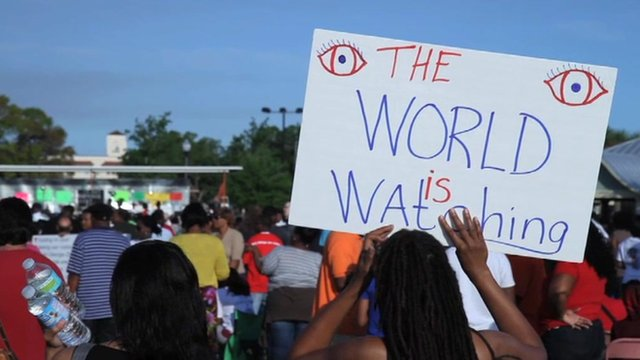 "Woman holds up sign which says ""The WORLD is watching""."