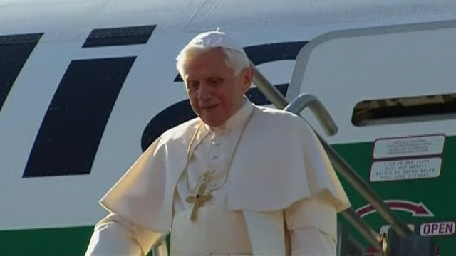 The Pope exits his plane on the runway after landing in Mexico.