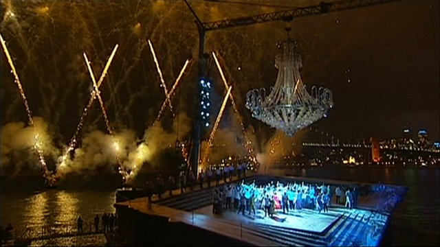Fireworks are launched around a floodlit opera staged at night on a massive open air barge.