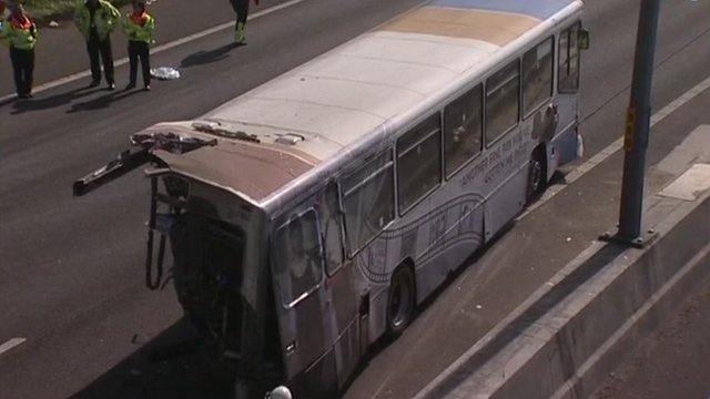Coach on road after crash, with one end mangled.