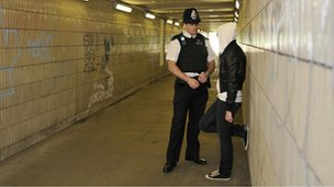 A policeman talking to a girl in an underpass
