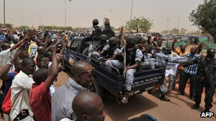 Malian military junta supporters surround a car loaded with soldiers at Bamako airport.