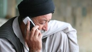 Middle aged Afghan man on his mobile phone in Kabul