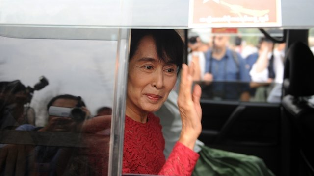 Aung San Suu Kyi waves at supporters at a polling station in Kawhmu