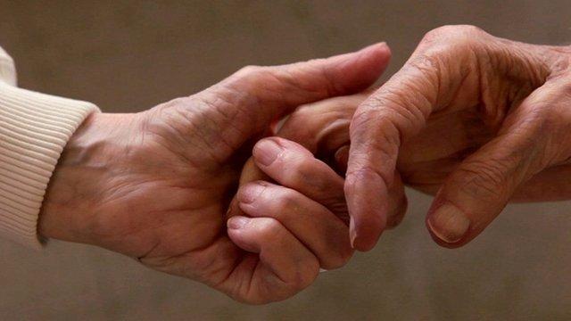 A close up of elderly women holding hands