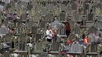 A man fires a confetti popper among tombstones at a public cemetery in Jinjiang, Fujian, 3 April 2012