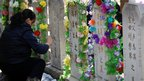 A women repaints the characters on the tombstone of her family grave at a cemetery in Beijing, China, 4 April 2012